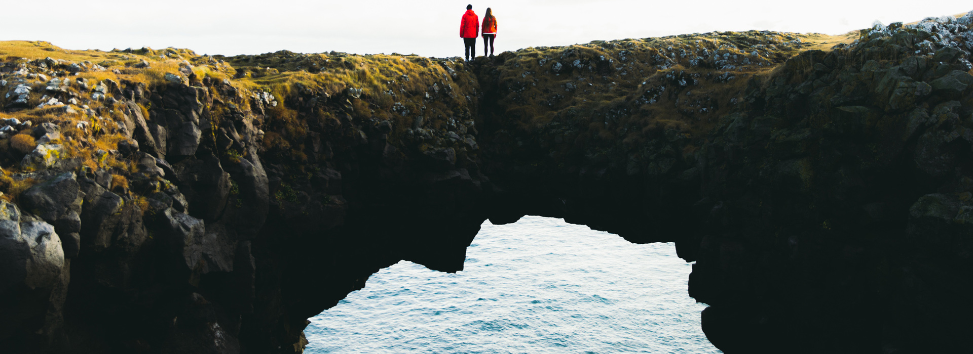 People standing on top of Gatklettur-Arch Rock in Snaefellsnes peninsula, Iceland