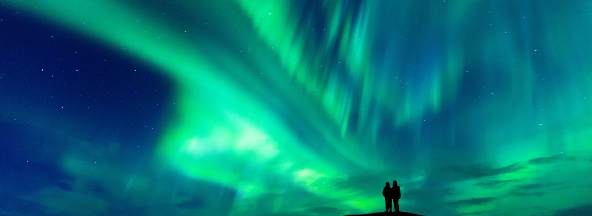 Aurora Borealis with silhouette of a romantic couple, Iceland
