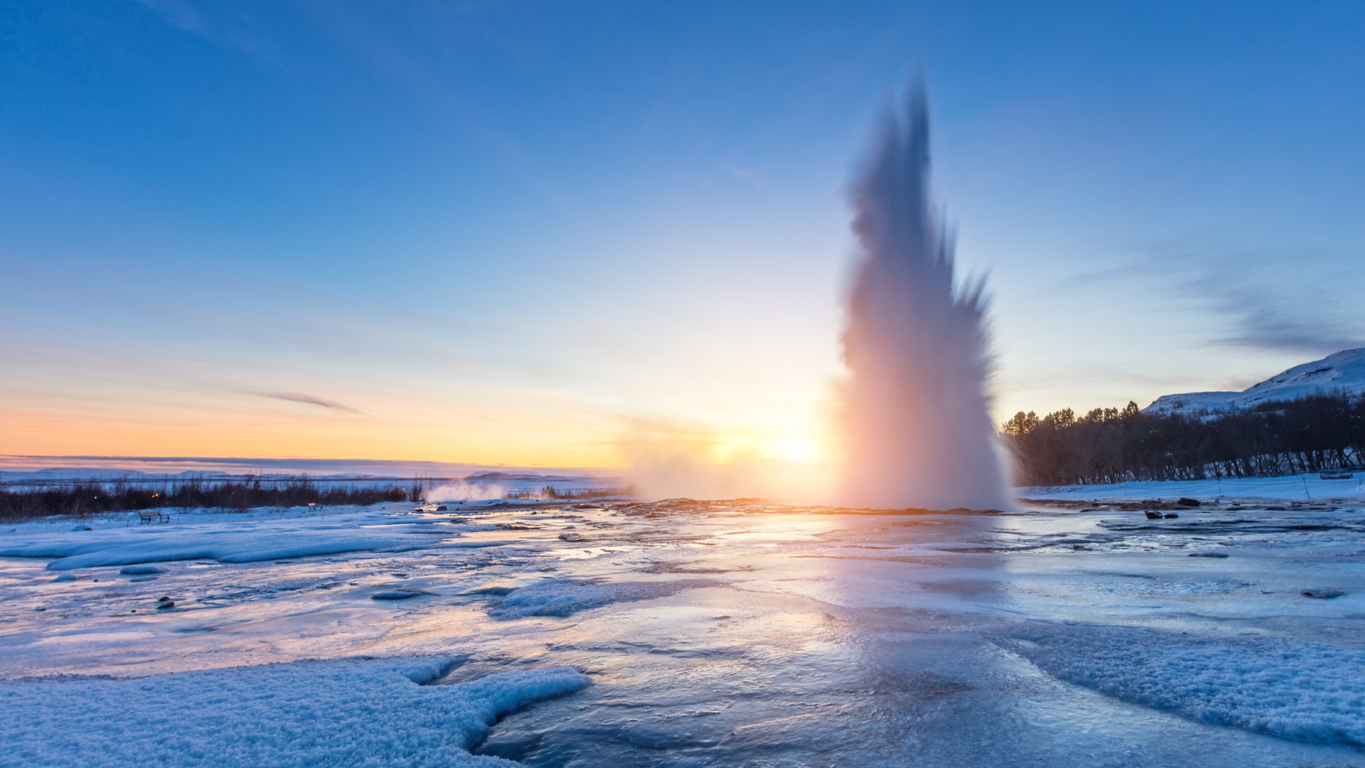 The Strokkur geyser erupting, surrounded by frozen ice.
