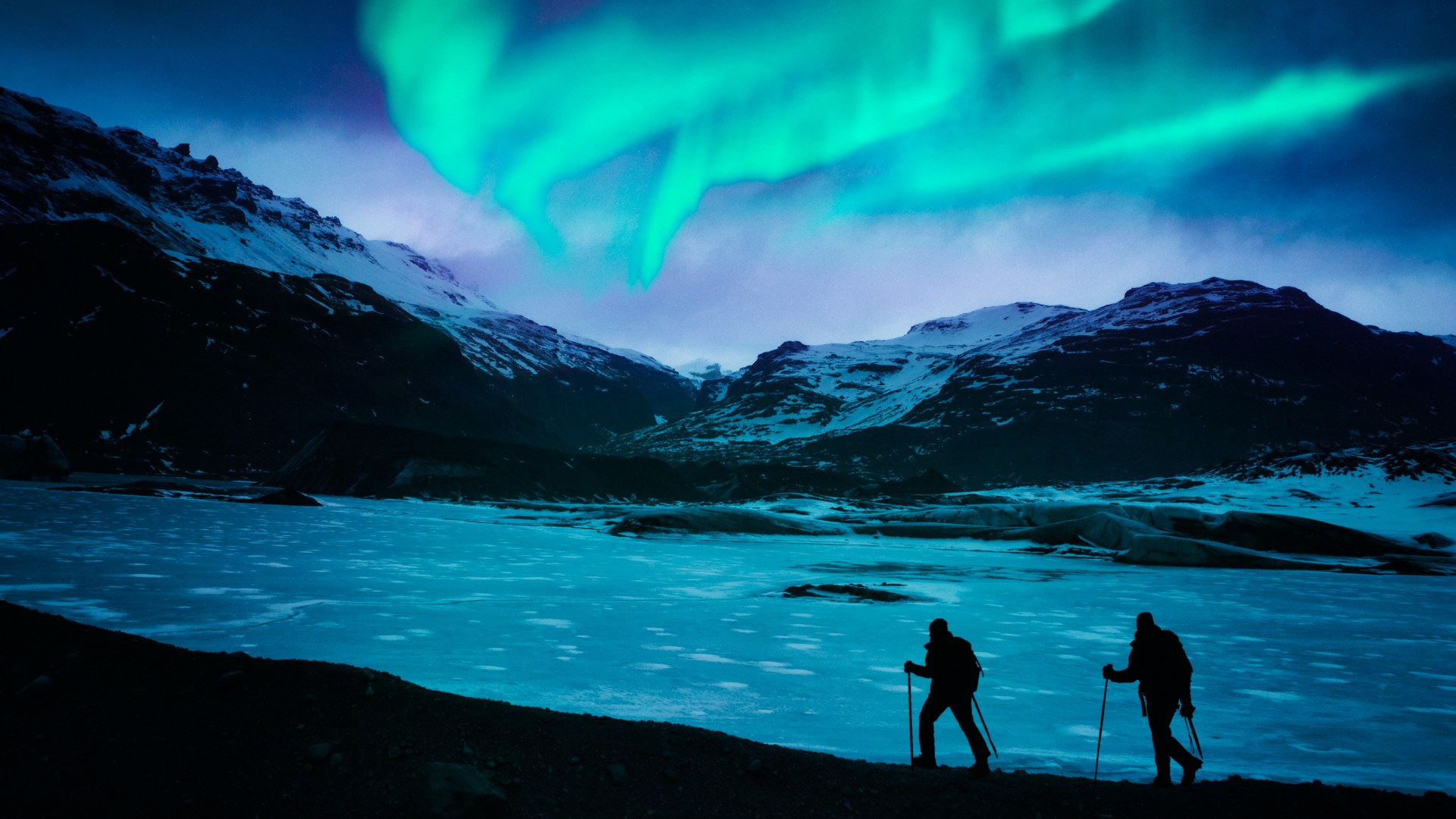 Hikers under the magical turquoise Northern Lights in Iceland.