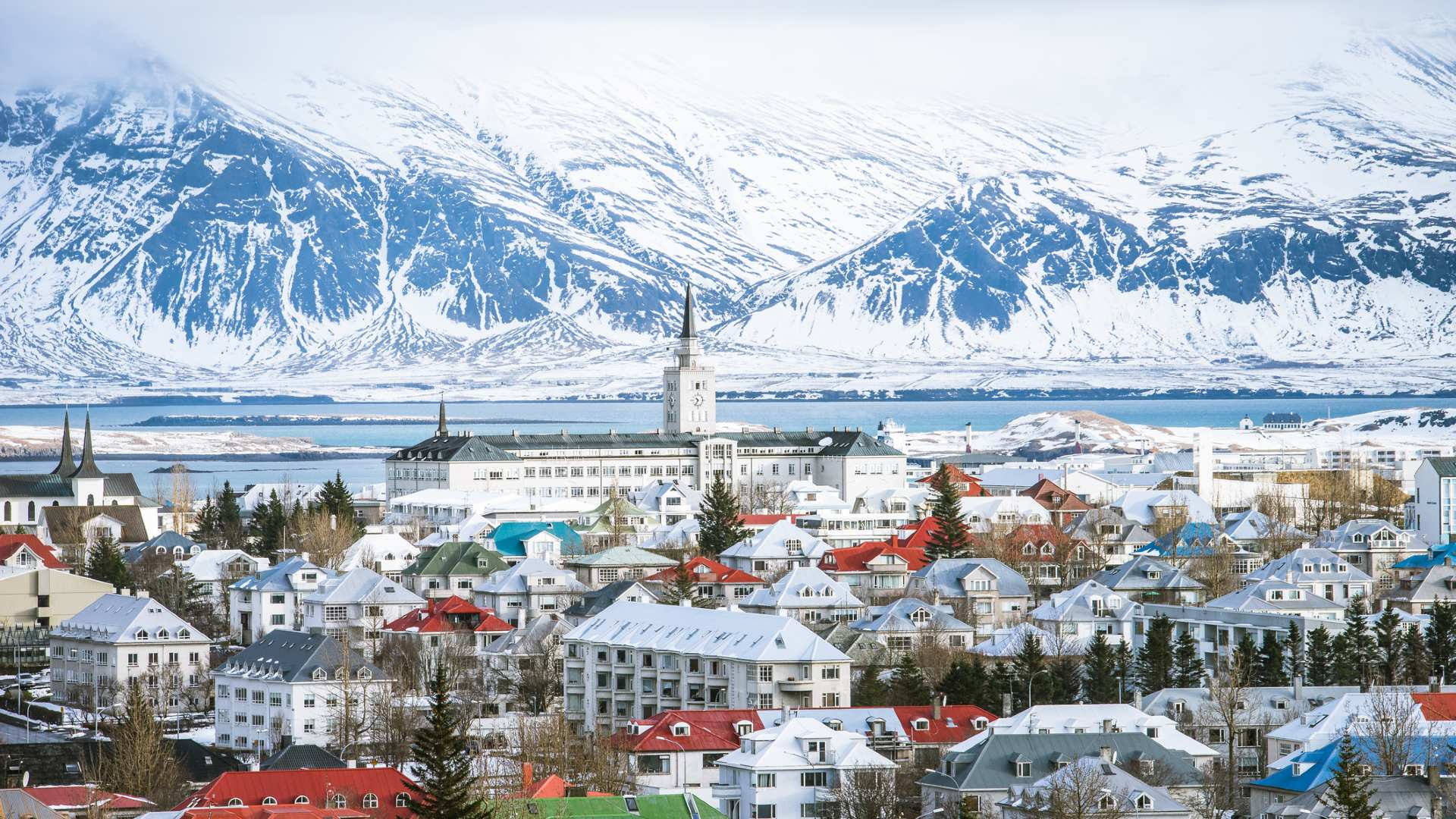 A wintry Reykjavík with the snowy Esja mountain in the background.