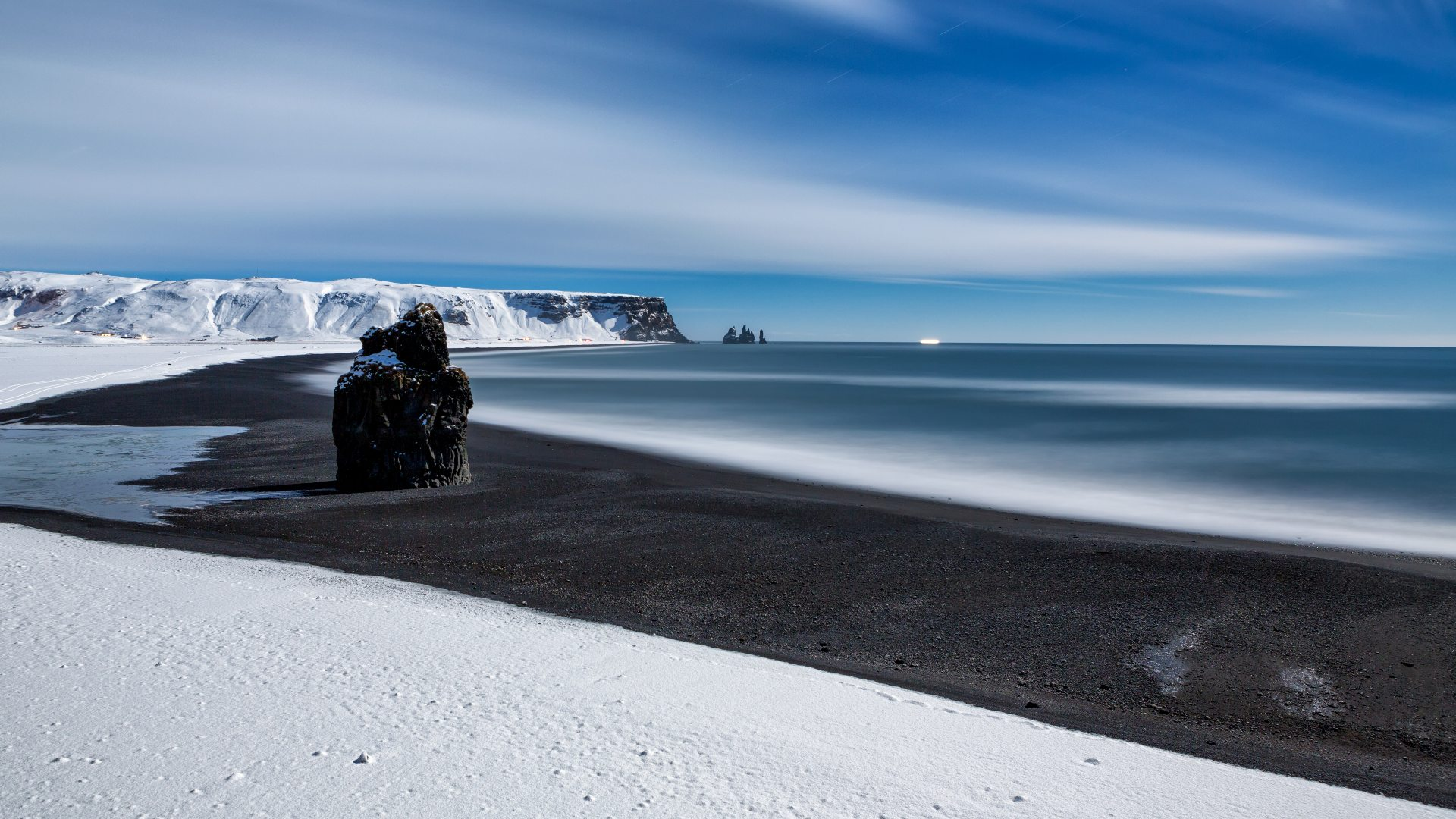 The Reynisfjara black sand beach covered in snow, with the Reynisdrangar rock formation in the distance.
