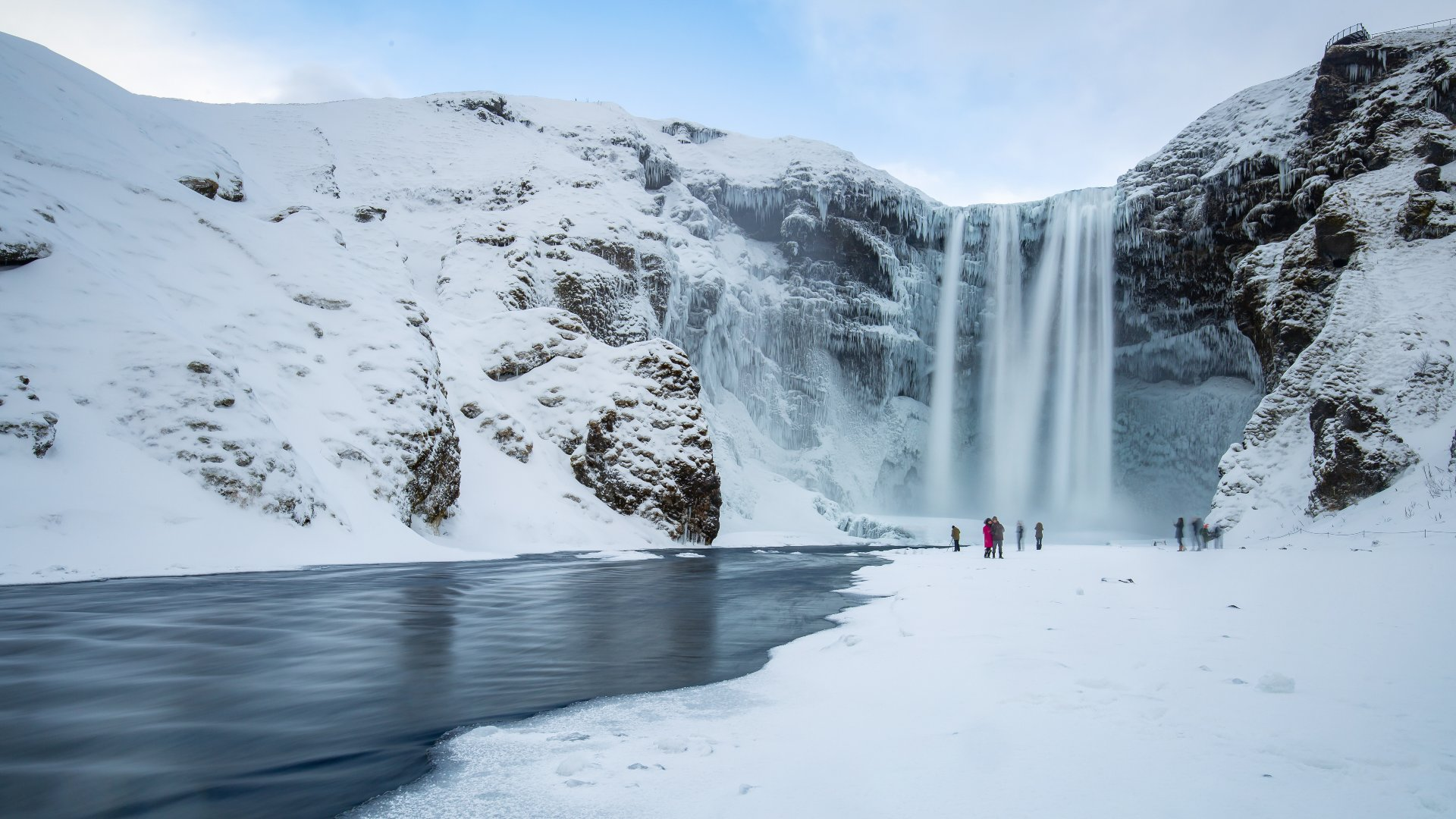 The Skógafoss waterfall surrounded by snow and ice.